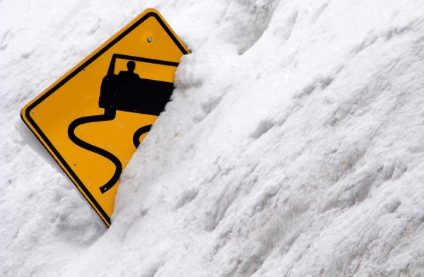 Slippery Road Sign half buried in snow