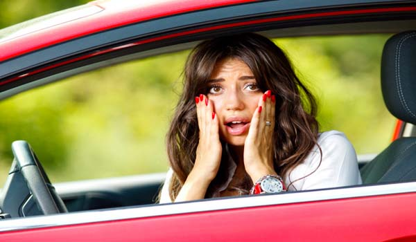 Young pretty scared woman in the car